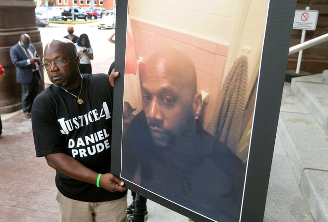 Joe Prude holds an enlarged photo of his brother Daniel, who was killed during an arrest by the Rochester Police Department.