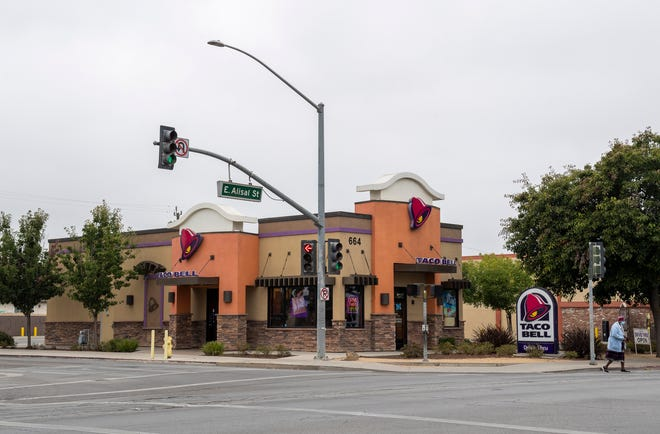 A Salinas resident walks in front of the Taco Bell where the now-viral photo of the two girls using WiFi in a parking lot was taken. This photo was take early morning in Salinas, Calif., on Tuesday, Sep. 1, 2020.