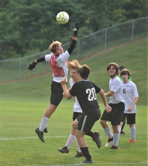 A Tri-Valley shot sails over the hand of New Lex keeper Coltin Collins in Tuesday's soccer match at Kenny Wolford Park. Tri-Valley won 9-0.