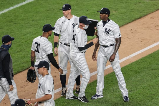 Aroldis Chapman and Yankees players gather on the field after Tuesday's win against the Rays.