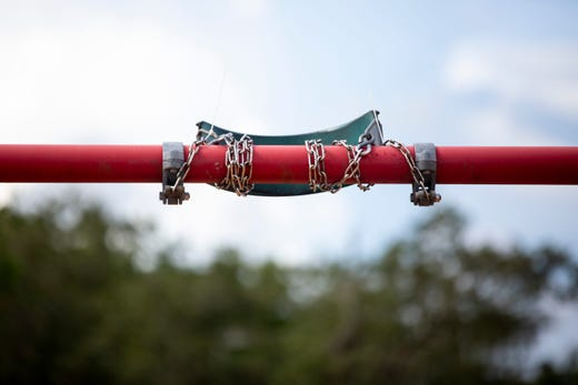 One of two swings is zip-tied to the top of the swing set in order to enforce distancing during a tour to highlight coronavirus precautions being implemented by Collier County Public Schools throughout the district at Mike Davis Elementary School near Golden Gate on Thursday, August 13, 2020.
