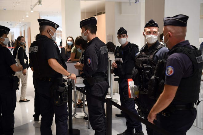 Policemen control people arriving at Paris' courthouse for the opening hearing of the trial of 14 suspected accomplices in Charlie Hebdo jihadist killings, on September 2, 2020. - Fourteen people accused of helping jihadist gunmen attack the French satirical weekly Charlie Hebdo and a Jewish supermarket go on trial, five years after days of terror that sent shockwaves through France.