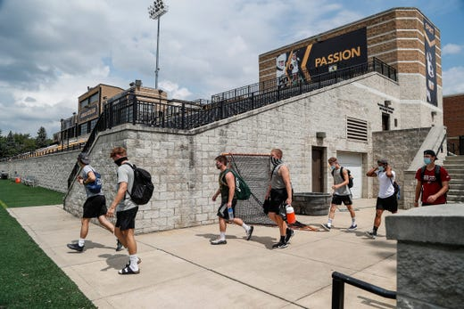 A group of football players walk down to the Kapnick Field for their workout at Docking Stadium of Adrian College in Adrian ON August 14, 2020.