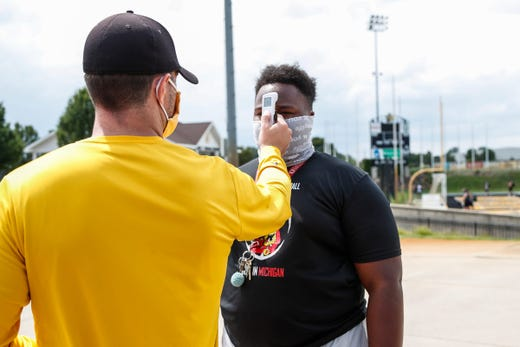 Offensive coordinator Harry Bailey takes freshmen guard Traviontae Ali's temperature before work out at Adrian College in Adrian on Aug. 14, 2020.