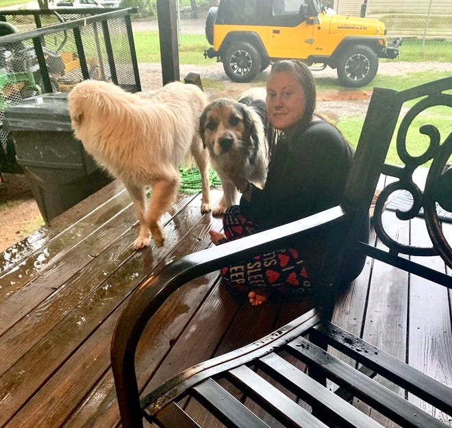 Courtney Kuhlman sits with the dogs she helped rescue from high waters during an immense amount of flooding in Ardmore on Tuesday.
