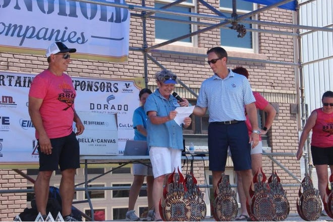 Former United Way of South Central Oklahoma Executive Director tobi Ervin announces the fundraising results of the 2019 BBQ Showdown as Kevin Lassahn holds the mike and Gino Silvas looks on