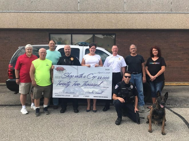 Ashland Downtown Dream Cruise and Car Show Committee members and police officers, from left, pose with a big checking, representing the money raised from the car show for the Shop With A Cop program. They are, Jim Berry, Tony Wittman, Chief Deputy Carl Richert, Lt. Craig Kiley, Sandra Tunnell, Chief Rick Anderson, John Grundy, Marla Helms. And in front are officers Tim Atchison and Robbie. Proceeds from the annual July event go to Shop With A Cop each year — $22,000 this year.