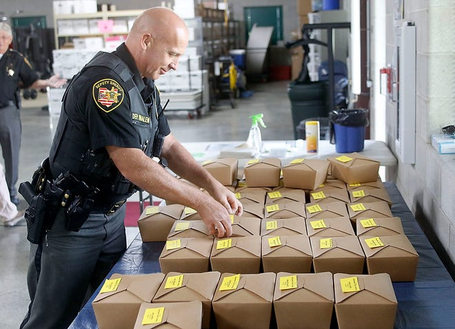 Ashland County Deputy Tim Whalen picks up his lunch  provided by Charles River Laboratories in Ashland for all of the Ashland County Sheriff Office staff on Thursday. There were boxed lunches delivered for all divisions of the Sheriff's Office as a thank you for the work do they do around the county.