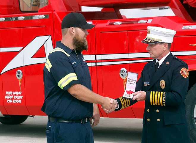 Aber's Towing and Crane Service driver Derrick Hamilton receives the Ashland Division of Fire's Civilian Medal of Honor from Chief Rick Anderson on Thursday for his actions during the July 29 quadruple fatal on Interstate 71.