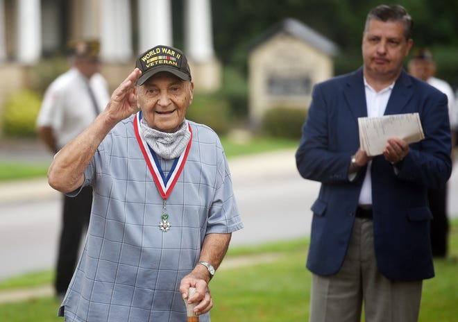Guy Prestia, 98, salutes the gathering of friends and family as the mayor of Ellwood City, Anthony Court looks on during a ceremony marking the 75th anniversary of the end of the war with Japan. The American Legion Post 57 laid a wreath on the monument at Legion Park Wednesday morning in Ellwood City. [Lucy Schaly/For BCT]