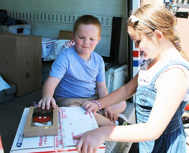 Laynee Reese, 9, helps her younger brother Huck open his package from heaven. Kim Archer/Examiner-Enterprise