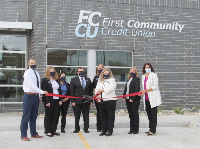 FCCU Crookston branch manager Dana Jonsson, with scissors, cuts the ribbon with local FCCU staff and, on the right, Crookston Chamber Executive Director Terri Heggie.
