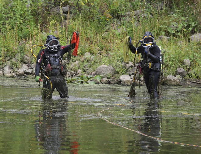 Divers from Enviroscience Inc. hold up nets with mussel collections from the shore of the Tuscarawas River in Massillon.