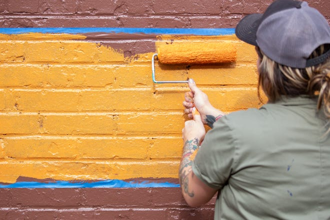 Whitney Herrington paints a new mural in Centerville, which was part of eight murals selected as part of 'Walls for Women,' a statewide project celebrating the 100th anniversary of the ratification of the 19th Amendment, which granted women the right to vote. (Courtesy photo)
