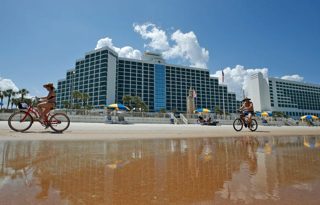 Visitors ride bicycles behind the Hilton Daytona Beach Oceanfront Resort in Daytona Beach. The hotel will be hosting a Job Fair on Wednesday, July 14, at the hotel, 100 N. Atlantic Ave., Daytona Beach.