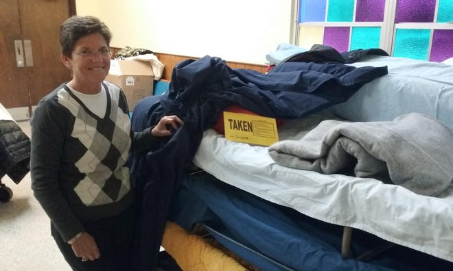 Sheltering Tree volunteer Vicky Le Tellier uncovers one of the cots that will be used during the cold winter night, January 2018.  (News-Journal file)