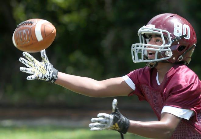 Trinity Christian Academy player Blaine Bissoondutt pulls in a pass as the team runs drills on Aug. 24.