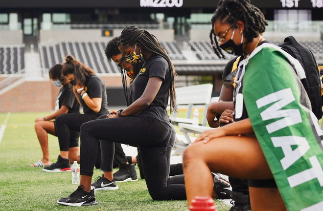 Members of the Mizzou Black Student Athlete Association take a knee on Faurot Field during the March With Mizzou protest on Wednesday evening.
