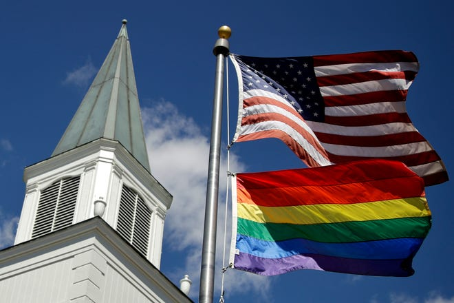 A gay pride rainbow flag flies along with the U.S. flag April 19, 2019, in front of the Asbury United Methodist Church in Prairie Village, Kansas. Had there been no COVID-19 coronavirus pandemic, America's largest mainline Protestant denomination would be convening in May 2020 for a likely vote on breaking up over differences on same-sex marriage and ordination of LGBTQ pastors.