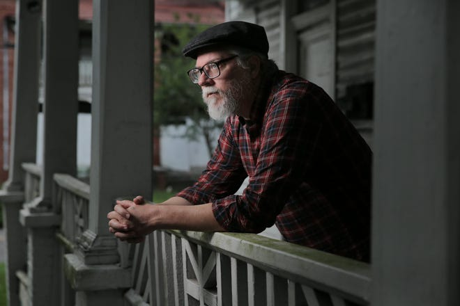 """Florida State College at Jacksonville Professor and author Tim Gilmore, whose latest book is titled """"Murder Capital: 8 Stories, 1890s-1980s,"""" peers from the porch of a Springfield home where Jacksonville serial killer Ottis Toole once lived."""