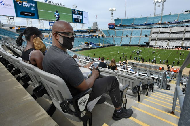 Jackie and Ronald Penn wear their masks as they watch a Jaguars scrimmage at TIAA Bank Field. Jackie was wearing a disposable mask under her cloth one that hangs from her ear. Accommodations have been made at the stadium to help reduce the chance of spreading the coronavirus. Among other things, seating capacity is limited and much of the available seating has been closed off to encourage social distancing.