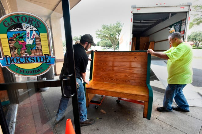 Employees move furniture out of Gator's Dockside, 8650 Baymeadows Road in Jacksonville on Wednesday -- one day after the restaurant closed permanently after 25 years in business.