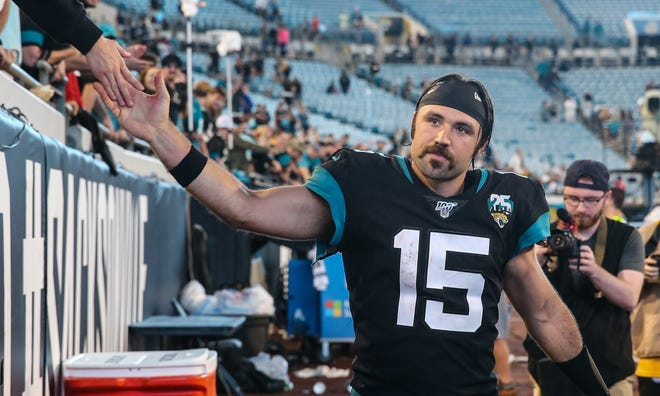 Jacksonville Jaguars quarterback Gardner Minshew II (15) high-fives fans after leading the team to a 38-20 victory over the Indianapolis Colts to end the 2019 regular season in Jacksonville.