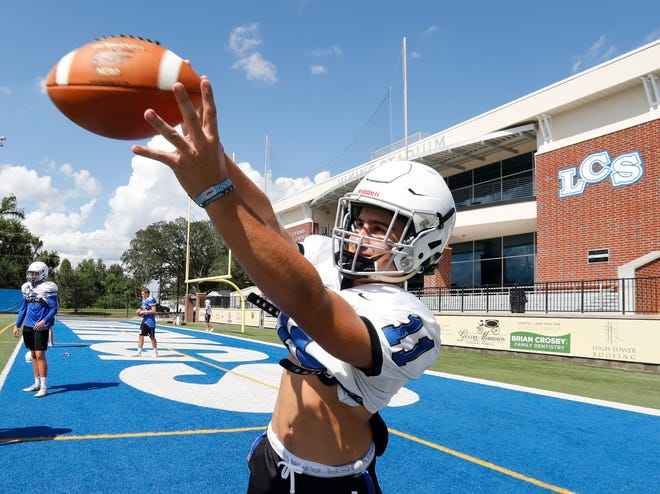 Wide receiver Blake Tyson pulls in a pass during football practice at Lakeland Christian School.