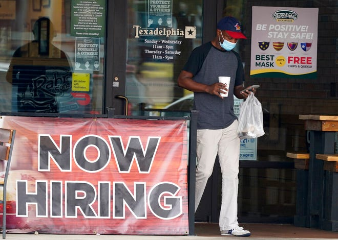 In this Sept. 2 photo, a customer walks past a now hiring sign at an eatery in Richardson, Texas. The number of laid-off Americans applying for unemployment benefits fell to roughly 880,000 last week, a sign of possible improvement but evidence that the viral pandemic keeps forcing many businesses to slash jobs,  the Labor Department reported Thursday.