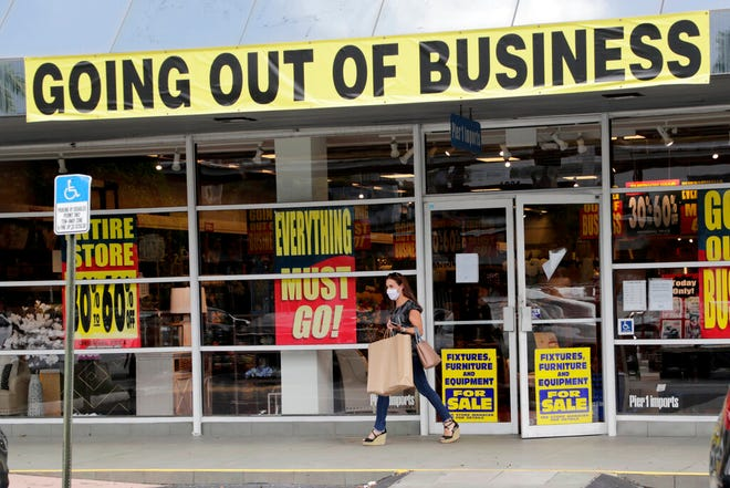 In this Aug. 6 file photo, a customer leaves a Pier 1 retail store, which is going out of business, during the coronavirus pandemic in Coral Gables. The number of laid-off Americans applying for unemployment benefits fell to roughly 880,000 last week, a sign of possible improvement but evidence that the viral pandemic keeps forcing many businesses to slash jobs.