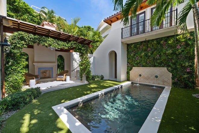 The poolside loggia has a gas-powered fireplace at 444 Chilean Ave. in Midtown. The pool's fountain abuts the garage-and-guesthouse. The lake-block proprty is listed for sale at $5.995 million. [Pagoda Photography photo courtesy Sotheby's International Realty]