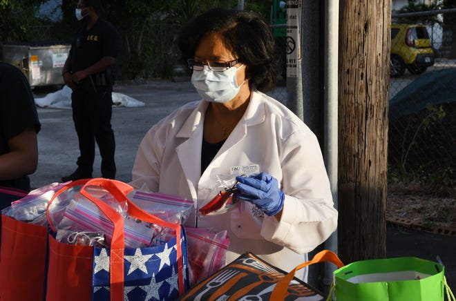 WEST PALM BEACH -- Dr. Karethy Edwards and other members of the Florida Atlantic University College of Nursing help distribute hundreds of handmade face masks at the Tabernacle Baptist Church in May to help at-risk communities prevent the spread of the COVID-19 virus.  [JIM RASSOL/palmbeachpost.com]