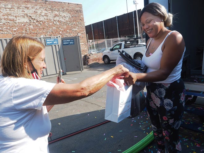 "Mary Jarrard, founder of Shower With Love Mobile Showers, left, gives Tierra Womack a goodie bag for taking the 2,000th shower in the facilities. The organization was started five years ago to offer free showers to people displaced in the community. ""This is for our homeless community to be able to stay clean. They are able to use the showers that have social distancing in place, and all the showers are sanitized between each shower,"" Jarrard said. In addition to the showers, clothes and shoes are offered to anyone in need. The mobile showers have four locations they visit each week: Monday at Gravity Church in Lodi, Tuesday at Stockton Alliance Church, Wednesday at The Word Church in Stockton and Thursday at St. John's Episcopal Church in Stockton. Times for all are 8 a.m.-12:30 p.m. ""If someone wanted to,"" Jarrard said, ""they could follow us and get four showers a week."""