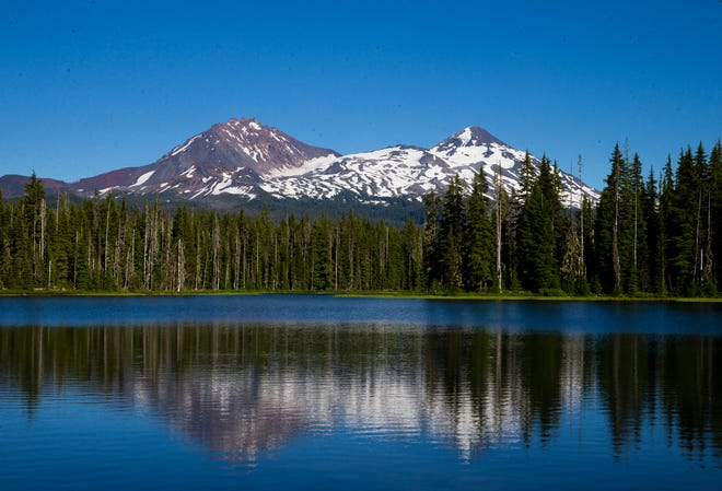 The North and Middle Sister are reflected in the water of Scott Late in the Oregon Cascades.