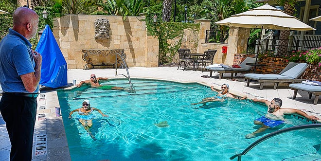 Charlie Robles, General Manager of the Collector Luxury Inn and Gardens in St. Augustine, talks to guests swimming in his hotel's pool on Thursday.