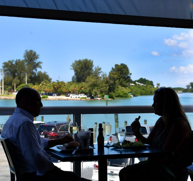 The Crow's Nest Restaurant & Marina offers an outdoor dining area with a view of the Venice Inlet.