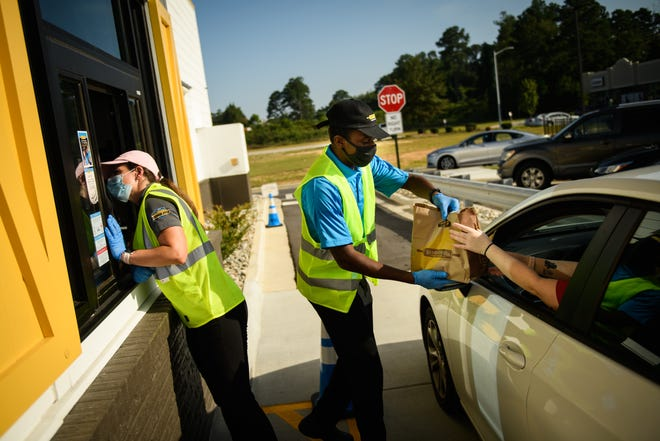 Alicia Gentile, left, and Ken Shelton hand out orders to customers at the grand opening of Biscuitville on Hope Mills Road in Hope Mills on Wednesday.