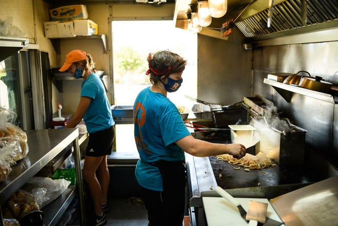 Madeline Russell, left, and Kayla Mundell do some prep work before the R Burger food truck opens for the lunch crowd.