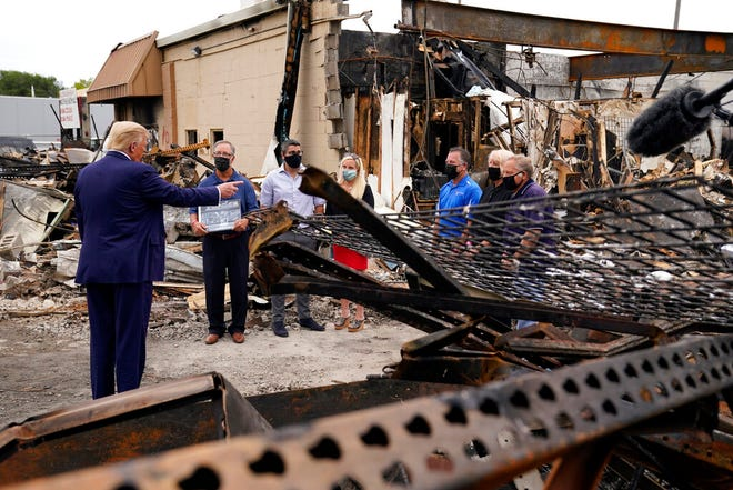 President Donald Trump talks to business owners Tuesday, Sept. 1, 2020, as he tours an area damaged during demonstrations after a police officer shot Jacob Blake in Kenosha, Wis. (AP Photo/Evan Vucci)