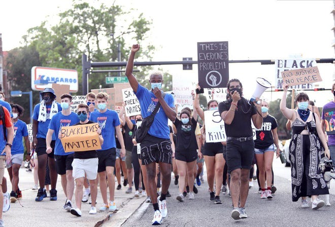 Florida basketball player Scottie Lewis (middle in blue) leads a march for social justice in Gainesville last Friday.