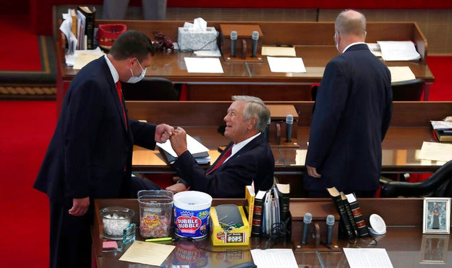 Rep. Jeffrey Elmore, left, fist bumps Rep. William Brisson as Rep. Michael Wray stands to the right, on the first day of a special session Wednesday, Sept. 2, 2020 in Raleigh, N.C.  (Ethan Hyman/The News & Observer via AP)