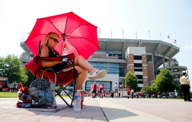 Tracy Baxter from Prattville uses an umbrella to shade herself as she sits and waits for the Walk of Champions outside Bryant-Denny Stadium. Fans look for a way to keep cool during tailgate time before Alabama's game with New Mexico State Saturday, Sep. 7, 2019. [Staff Photo/Gary Cosby Jr.]