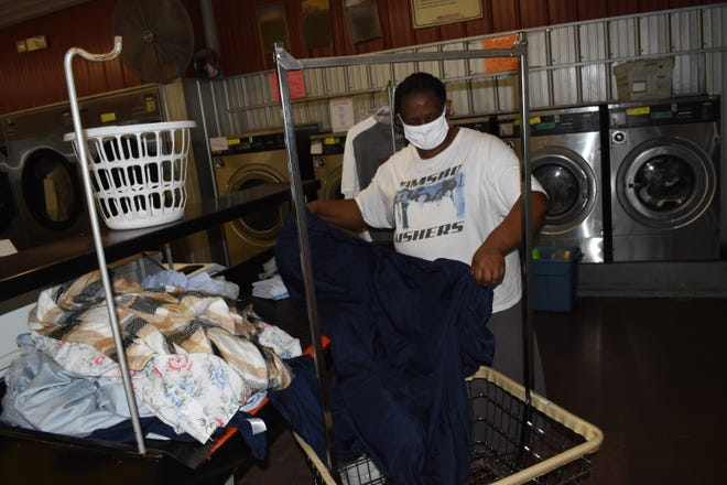 "Hattie Bruins folds laundry at Washland in Pineville. She thinks Tide Loads of Hope is a nice thing to do for help people after Hurricane Laura wreaked havoc in the area. Tide Loads of Hope is activating free ""pop-up"" laundromat services in Alexandria and Pineville for those affected by Hurricane Laura."