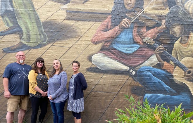 Clay studio manager Charles Freeland, Program Coordinator Maryleee Rorick, Executive Director Lori Cozzi and Events Coordinator Jessica Klarp stand in front of a recently installed mural outside the Black Mountain Center for the Arts.