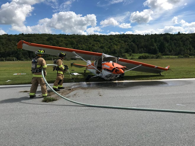 Firefighters douse the Cessna 170A that crashed at Morrisville-Stowe State Airport on Thursday morning, injuring two people.