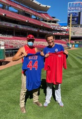 Anthony Rizzo, right, swaps jerseys with Cincinnati Reds grounds crew member Alex Polnow after the Chicago Cubs played the Reds on Sunday, Aug. 30, 2020, at Great American Ball Park.