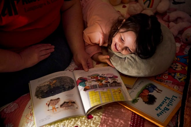 Mary Osterhoudt, 4, giggles while her mother, Marisa Sikes, reads books provided by Imagination Library to her aloud during their evening routine at their home in Clarksville, Tenn., on Wednesday, Sept. 2, 2020.