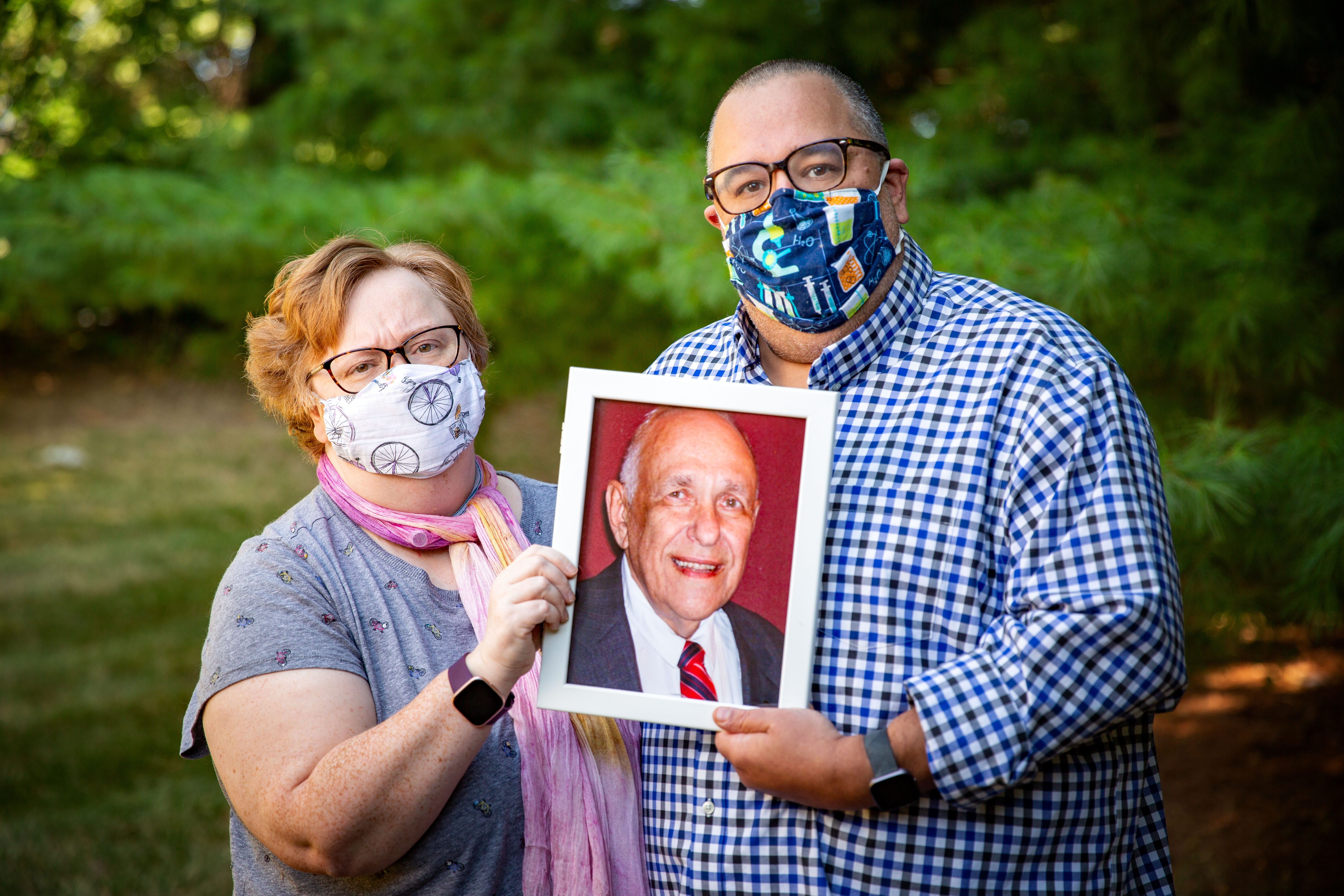 Ross Daniels and his wife, Amy, poses for a photo with a portrait of his father, Jay Daniels