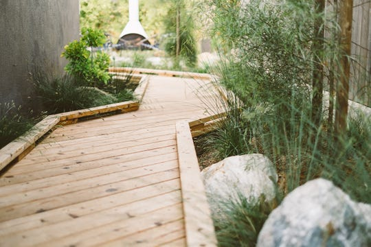 """""""There is something about walking along a linear wood bridge that is deeply satisfying,"""" says Ryan Prange, designer of this rain garden in Encinitas, California. The footbridge in the side yard of this garden is over a bioswale, designed to improve drainage on the lot."""