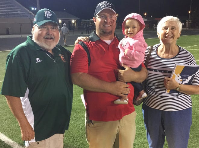 Forest Park head football coach Ross Fuhs poses with his daughter Carly, father Charlie (left) and mother Cindy (right).
